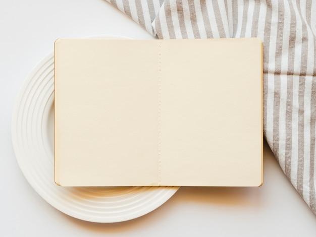 Lichtbruin schetsboek op een witte plaat op een witte achtergrond met een gestreept grijs en wit tafelkleed Gratis Foto