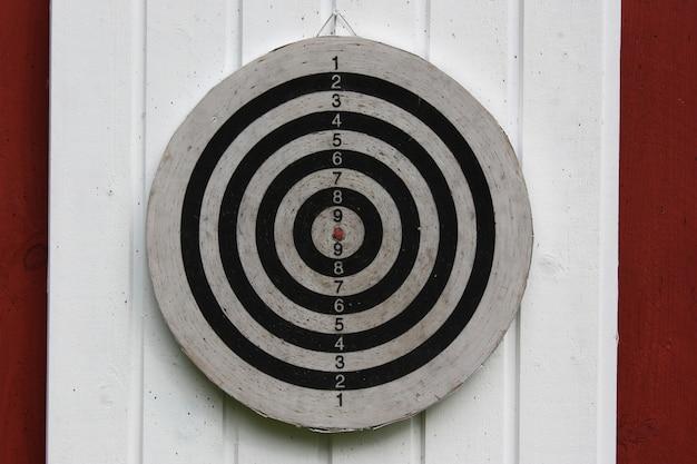 Lichte close-up shot van een dartbord gehangen op een witte en rode muur Gratis Foto