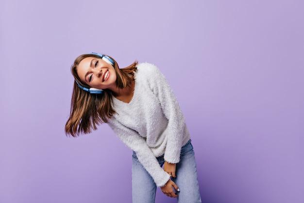 Lichte jonge dame die voorover leunt, ontspannen en vriendelijk lacht. portret van vrouwelijke student in blauwe moderne hoofdtelefoons Gratis Foto