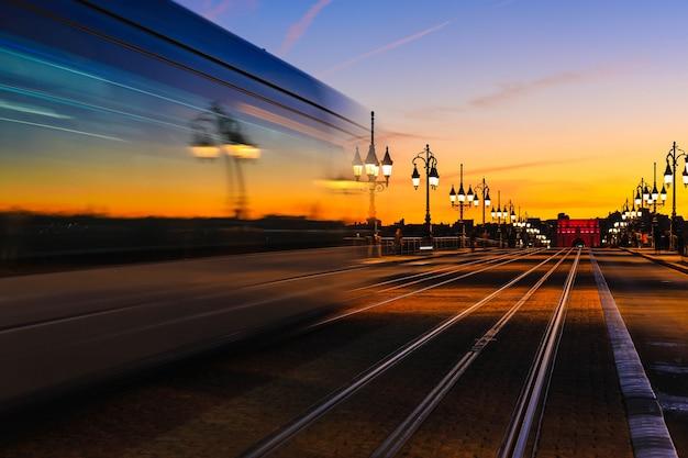 Lichte paden van tram op pont de pierre stenen brug over de rivier de garonne in bordeaux Premium Foto