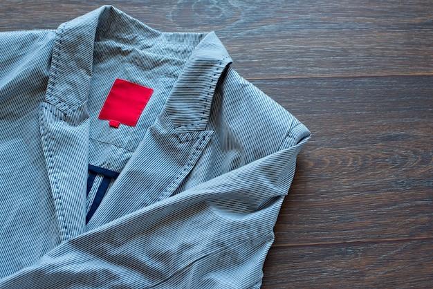 Lichtgewicht gestreepte katoenen jas met een modieuze broche op houten achtergrond Premium Foto