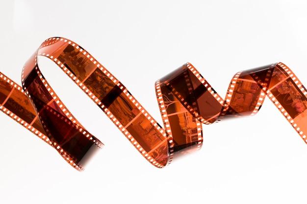Lichtjes gerolde onontwikkelde filmstrook die op witte achtergrond wordt geïsoleerd Gratis Foto