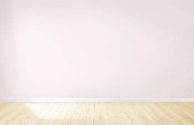 Lichtroze muur in een lege ruimte met een houten vloer Gratis Foto