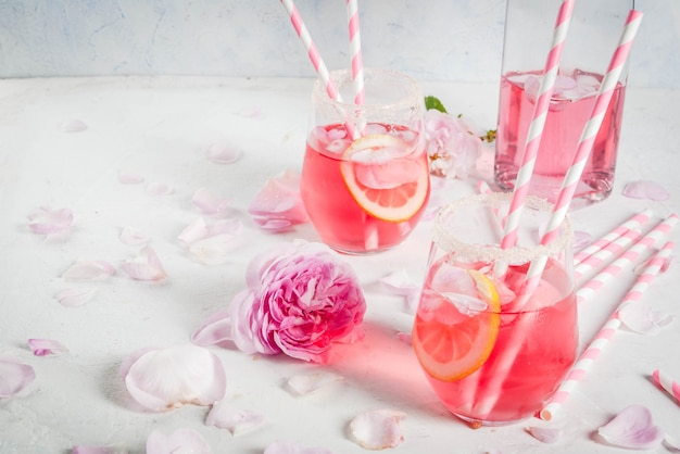 Lichtroze rose cocktail, met rose wijn, thee rozenblaadjes en citroen op een witte stenen betonnen tafel. Premium Foto