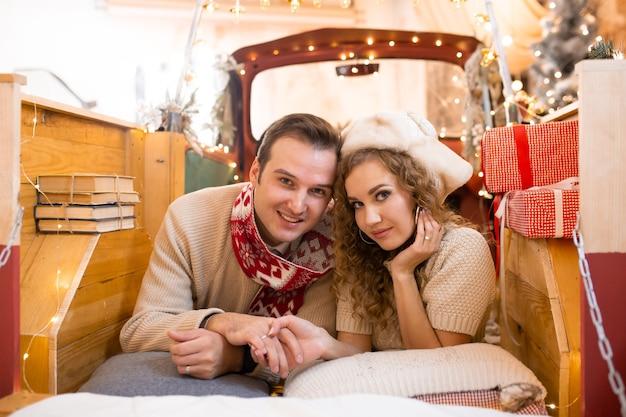 Lief plezier hebben en samen genieten van hun tijd in een pick-up auto. kerstverlichting op de achtergrond Premium Foto