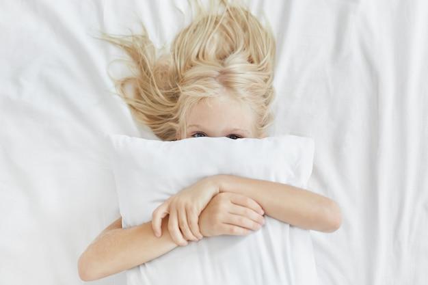 Lief schattig meisje met licht lang haar, verstopt achter wit kussen, omarmen terwijl liggend in bed, plezier in de ochtend Gratis Foto