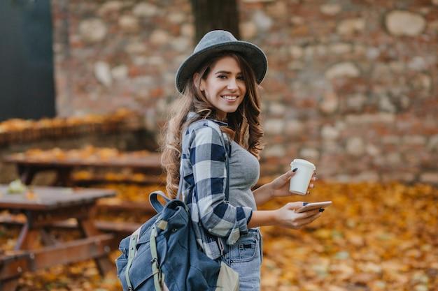 Lief wit meisje in een geruit overhemd met smartphone en kopje koffie in september park Gratis Foto