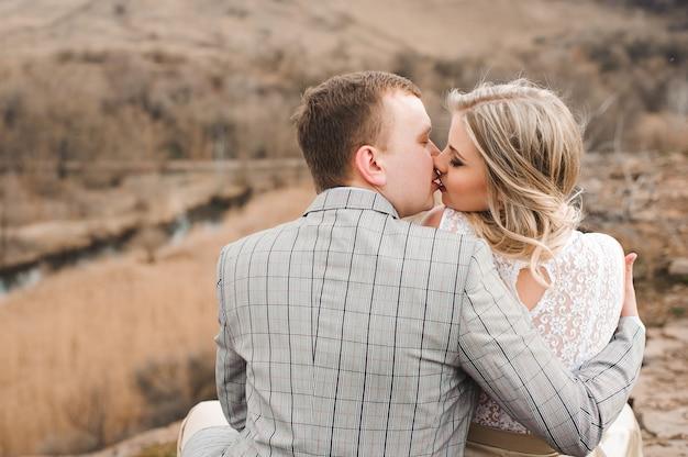 Liefde, romaans en mensenconcept - gelukkig jong paar die zitting op de rand van een klip in openlucht koesteren. Premium Foto