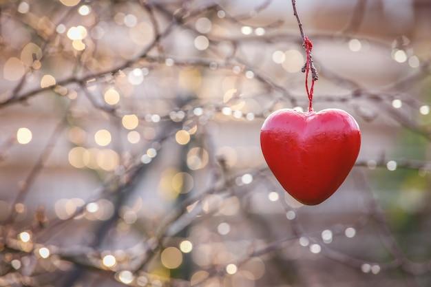 Liefdeconcept, de liefdesymbool van de hartvorm het hangen op takboom in wijnoogst met exemplaarruimte Premium Foto