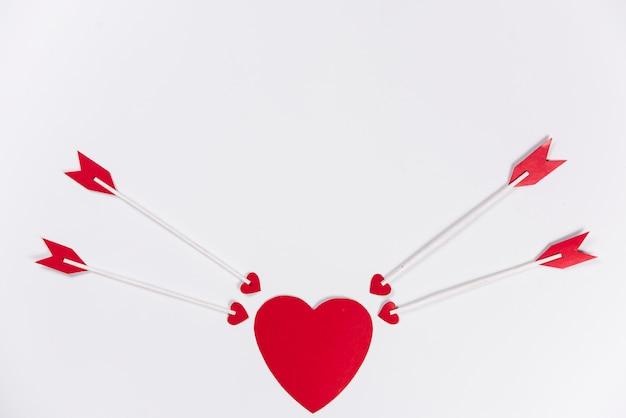 Liefdepijlen die naar rood hart streven Gratis Foto