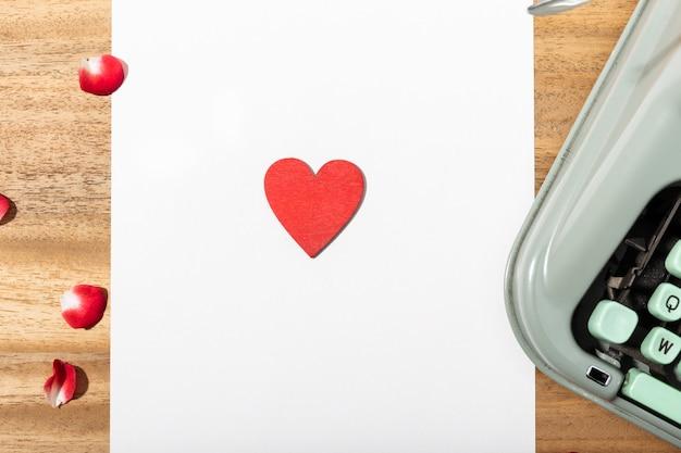 Liefdesbrief. bureau met blanco papier, retro typemachine en rood hart Premium Foto