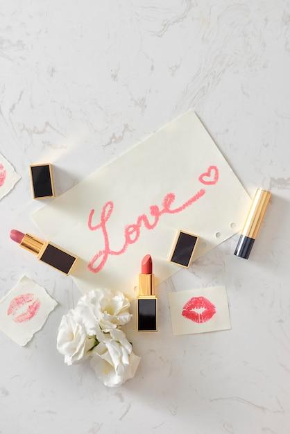 Liefdesbrief en lippenstiften op een marmeren tafel Premium Foto