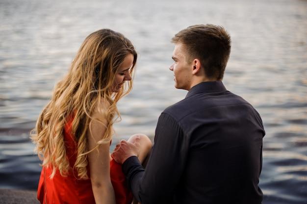 Liefdesverhaal van jong koppel op de achtergrond van water Premium Foto