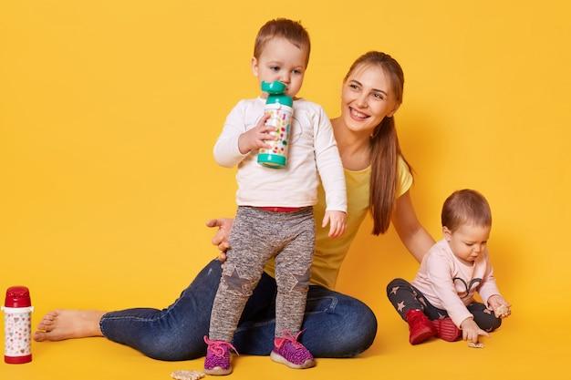Liefdevolle aantrekkelijke moeder zorgt voor haar kleine kinderen, tweeling speelt met mama. speelse kinderen drinken smakelijke drankjes uit haar bootle terwijl haar zus coockies eet. baby's hebben honger. Gratis Foto
