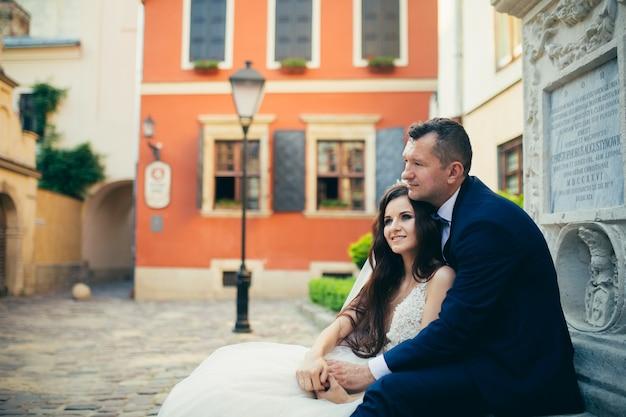 Liefdevolle bruidspaar knuffelen tegen de achtergrond van een prachtige stad Premium Foto