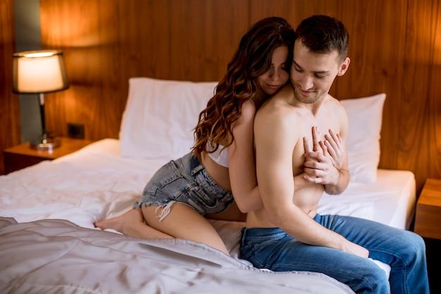 Liefdevolle en geknuffeld paar op het bed in de kamer Premium Foto