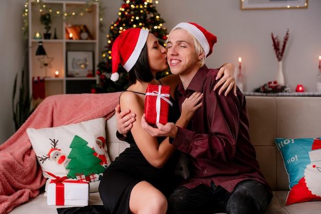 Liefdevolle jong koppel thuis in de kersttijd met kerstmuts zittend op de bank in de woonkamer die geschenken ontvangt Gratis Foto
