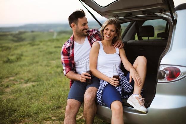Liefdevolle paar zitten in de auto trank tijdens reis in de natuur Premium Foto