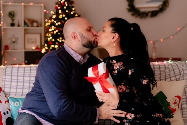 Liefdevolle romantische man en vrouw thuis in de kersttijd zittend op de bank in de woonkamer vrouw bedrijf geschenkpakket kussen op de lippen Gratis Foto