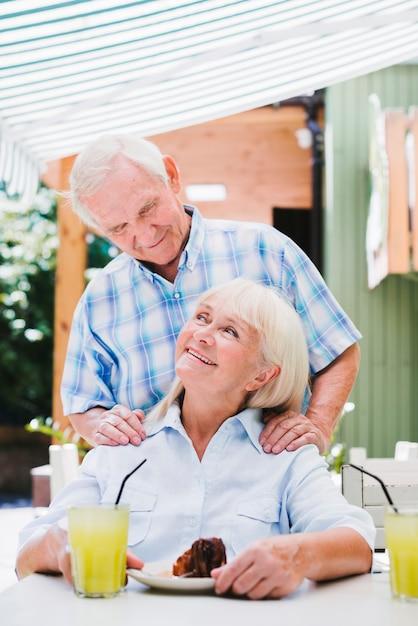 Liefdevolle senior koppel knuffelen in café op terras genieten van verfrissende drankjes Gratis Foto
