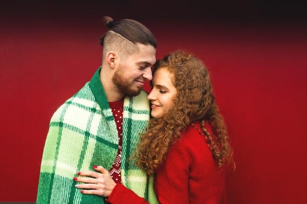 Liefhebbers knuffelen en glimlachen gelukkig in een gezellige kerstsfeer. Premium Foto