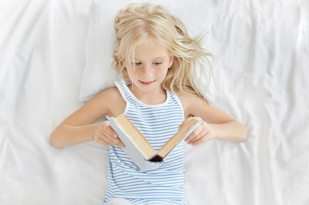 Lieve kleine blonde 7-jarige meisje van europese uitstraling rust in wit bed, op zoek in open boek met belangstelling tijdens het lezen van sprookje Gratis Foto