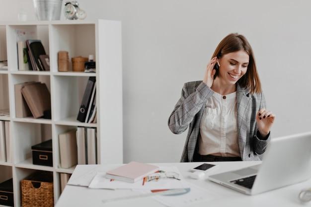 Lieve kortharige zakelijke dame lacht tijdens het luisteren naar muziek op de koptelefoon. portret van vrouw in bureaukleren die op werkplaats zitten. Gratis Foto