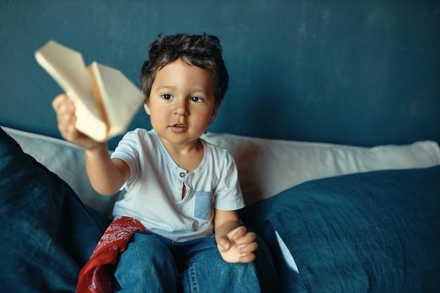 Lieve, mollige, donkere jongetje zittend op bed, actieve spelletjes spelen, papieren vliegtuigje gooien, opgewonden gelaatsuitdrukking hebben. Gratis Foto