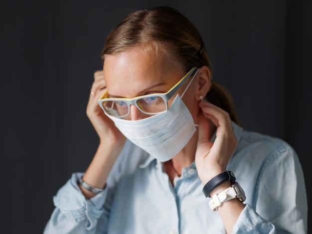 Lifestyle afbeelding. het mooie wijfje dat medisch masker thuis zet alvorens gaat op het werk. close-up shot. bescherm coronavirus. selectieve aandacht. covid-19 concept Premium Foto