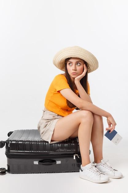 Lifestyle en reizen concept: jonge mooie blanke vrouw zit op koffer en wacht op haar vlucht. geïsoleerd over wit Premium Foto