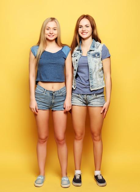Lifestyle portret van twee jonge meisjes beste vrienden springen over je heen Premium Foto