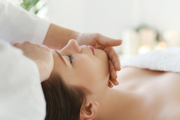 Liggende vrouw die een massage ontvangt. craniosacraal therapie Gratis Foto