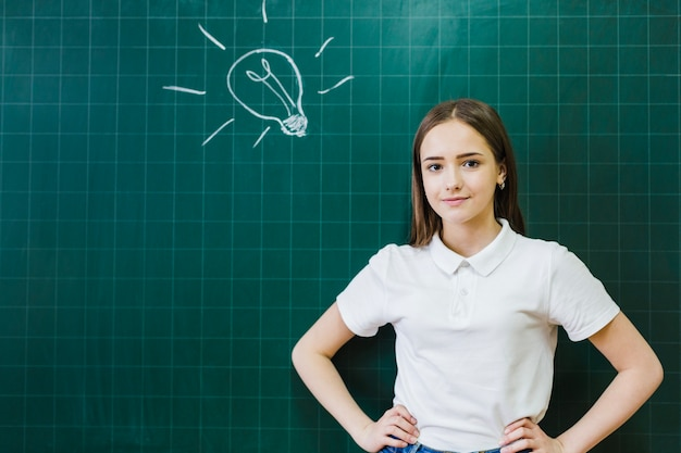 Ligh lamp op het schoolbord en student poseren Gratis Foto