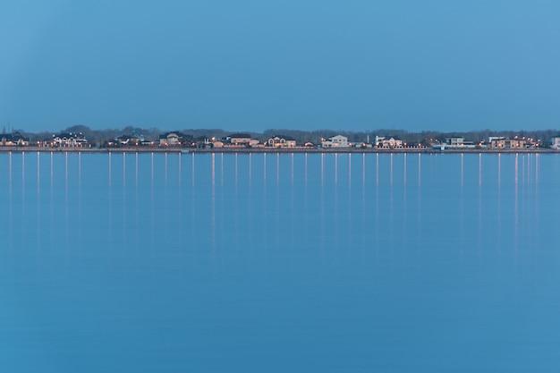 Lijn van woninghuizen op de horizon van de rivierkade Premium Foto