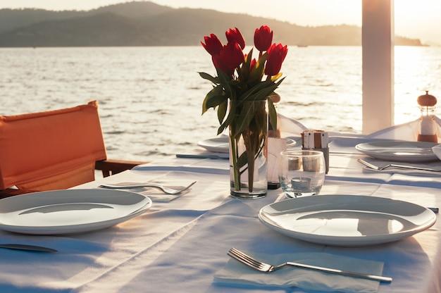 Lijst met bloemen bij strandrestaurant dat wordt geplaatst Premium Foto