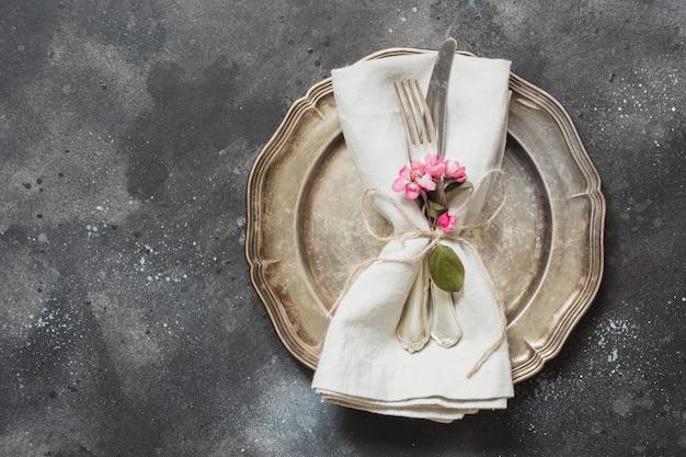 Lijstplaats het plaatsen met roze bloemen, tafelzilver op uitstekende achtergrond. Premium Foto