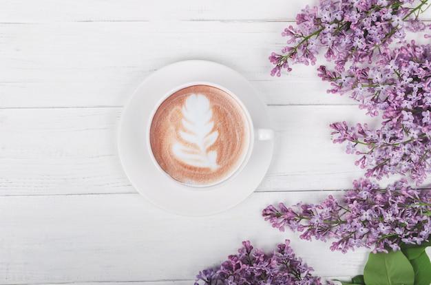 Lila, koffie met latte art op lichte houten tafel. romantische ochtend. plat leggen Premium Foto