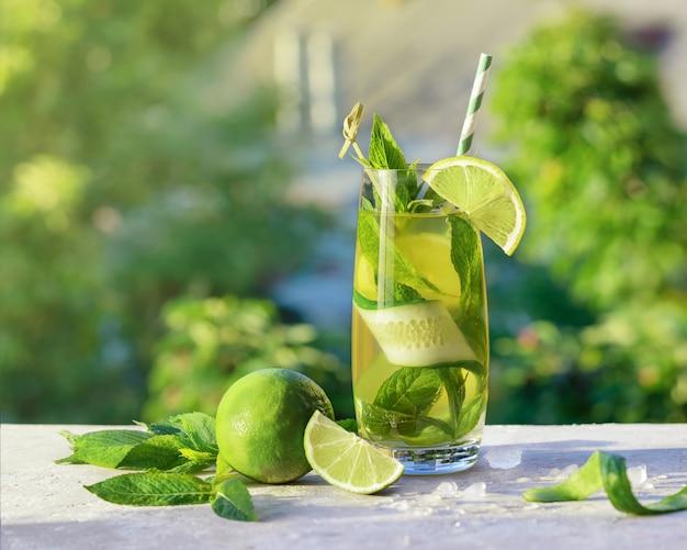 Limonade of mojito cocktail met limoen, komkommer en munt, koud verfrissend drankje of drankje met ijs, buiten. koud detoxwater met citroen en papierstro. zomer drankje met kopie ruimte. Premium Foto