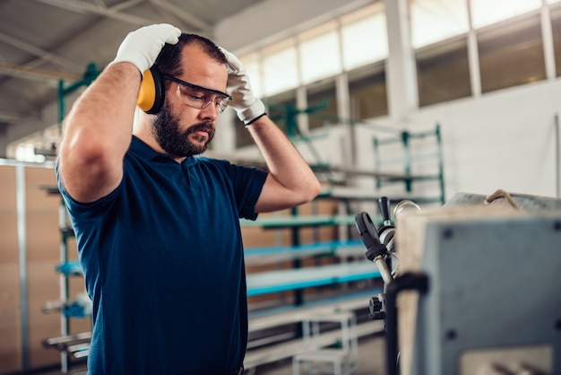 Lintzaag snijmachine werknemer het aantrekken van beschermende oorbeschermers Premium Foto