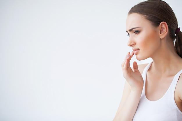 Lippenpijn, sluit omhoog portret van jong mooi peinzend meisje in witte sweater Premium Foto