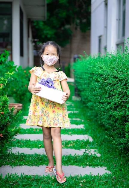 Litte aziatisch meisje dat masker in gele kleding draagt die huidige doos in haar verjaardag in het park houdt Premium Foto