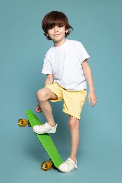 Litte jongen in wit t-shirt met skateboard op blauw Gratis Foto
