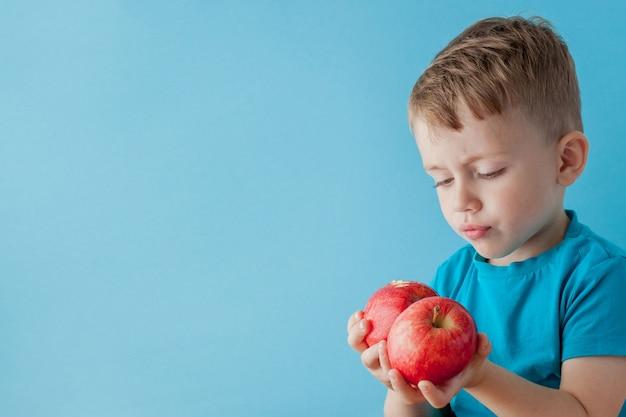 Little boy die appelen in zijn handen op blauwe achtergrond, dieet en oefening voor goed gezondheidsconcept houden Premium Foto