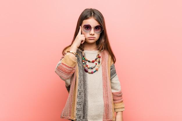 Little hippie meisje wijzende tempel met vinger, denken, gericht op een taak Premium Foto