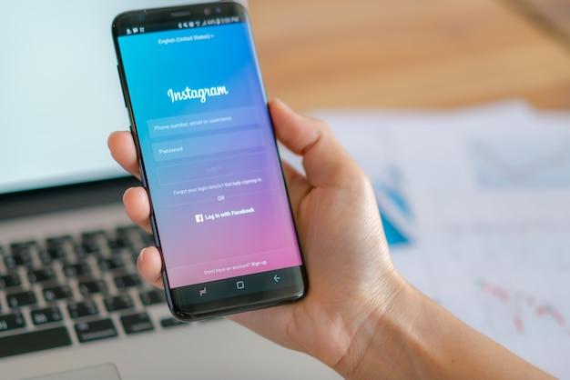 Loei, thailand - 10 mei 2017: hand met samsung s8 met mobiele applicatie voor instagram op het scherm. Gratis Foto