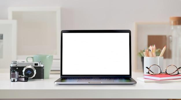 Loft werkruimte met leeg scherm laptop, vintage camera en kantoor aan huis levert Premium Foto