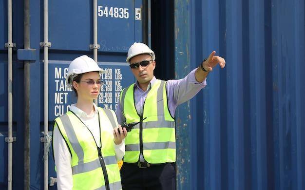 Logistiek ingenieur controle in de haven, containers laden voor vrachtwagens exporteren en logistiek concept importeren Premium Foto