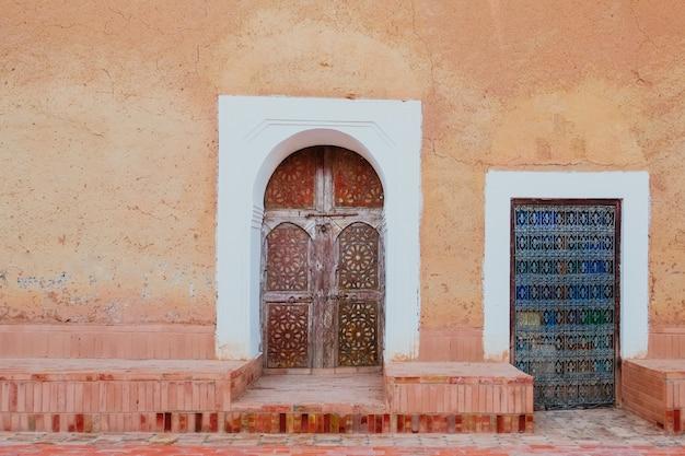 Lokale antieke marokkaanse patroon gesneden houten deuren tegen oude oranje roze muur Premium Foto