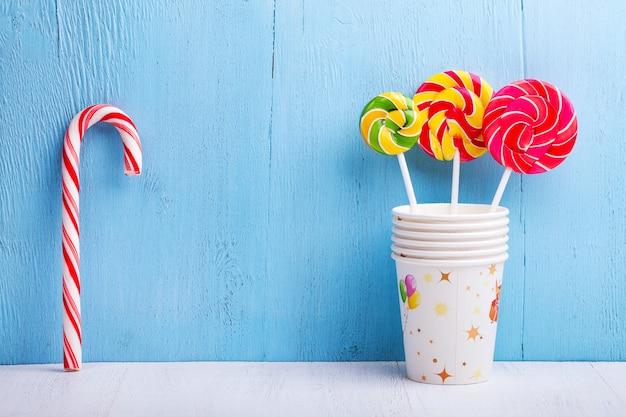 Lollies in cups met snoep stokken op blauwe houten muur Premium Foto