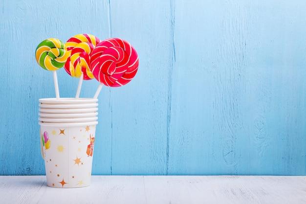 Lollies in cups op blauwe houten muur Premium Foto